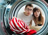 Man and woman looking inside dryer that has clogged dryer vent