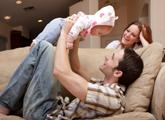 Dad holding up child on cleaned couch while mom watches