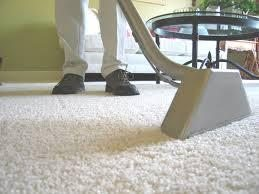 Legs and feet of technician steam cleaning white carpet