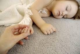 Child sleeping on clean gray carpet holding someone's hand