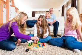3 girls playing a game on freshly cleaned carpet while mom and dad watch from the couch