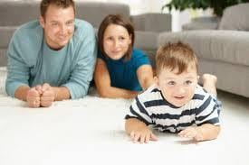Mom and dad laying on clean white carpet, watching child crawl