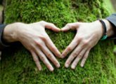 Hands peaking out from organic plant making heart sign