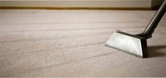 Steam cleaner working a white carpet, leaving clean lines
