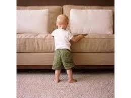 Toddler standing in front of clean couch