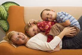 Mom and 2 kids laying on top of each other on orange couch that had upholstery cleaning by Peace Frog Carpet & Tile Cleaning in Austin