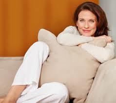 Woman on clean tan couch, clutching a pillow