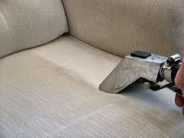Hand steam cleaning upholstery on couch. Stripe of clean area surrounded by dirty upholstery