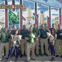 """Peace Frog employees standing in front of """"Greetings from Austin"""" wall graffiti"""