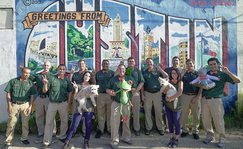 "Peace Frog employees standing in front of ""Greetings from Austin"" wall graffiti"