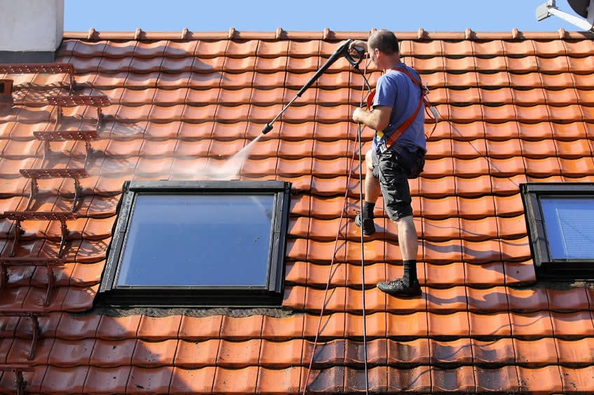 Man Washing The Roof Tiles - Pressure Washing Austin TX