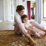 mom and daughter sitting on rug