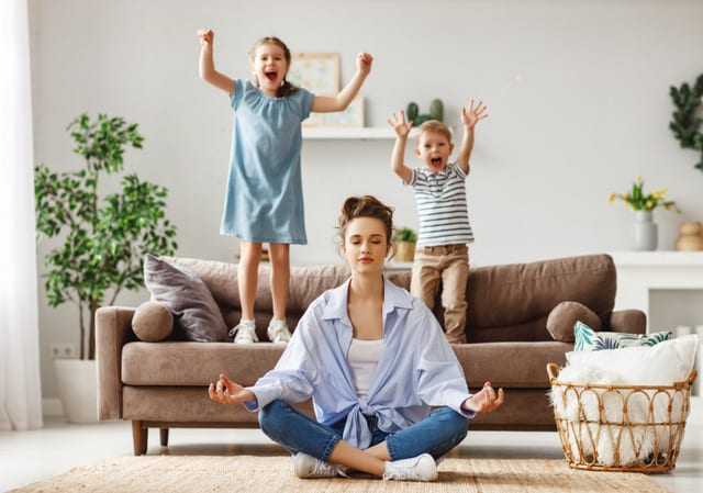 mom doing yoga while kids jump on upholstered couch